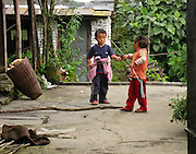 Two children play fight with sticks along the trail to Annapurna Sanctuary in Nepal, Asia.