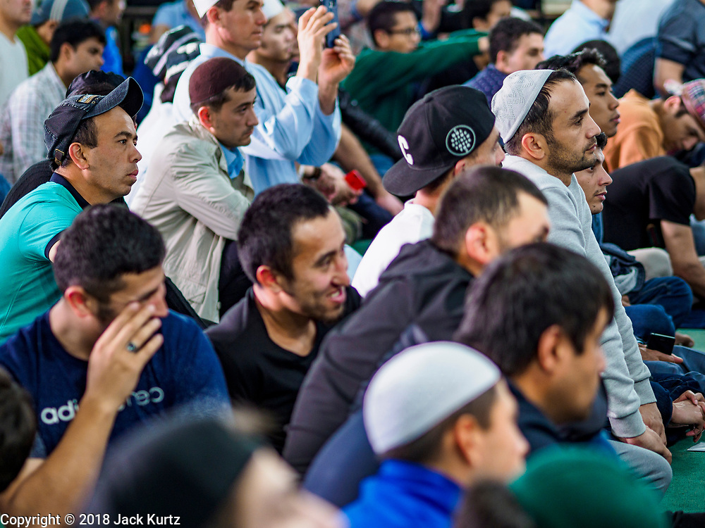 "15 JUNE 2018 - SEOUL, SOUTH KOREA: Men listen to the ""Khutbah,"" or sermon, at Seoul Central Mosque on Eid al Fitr, the Muslim Holy Day that marks the end of the Holy Month of Ramadan. There are fewer than 100,000 Korean Muslims, but there is a large community of Muslim immigrants in South Korea, most in Seoul. Thousands of people attend Eid services at Seoul Central Mosque, the largest mosque in South Korea.   PHOTO BY JACK KURTZ"