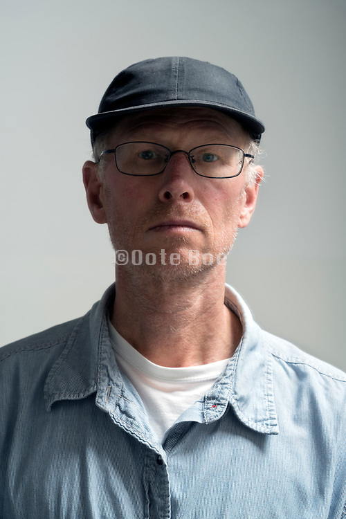 portrait of a 50+ years male person wearing a cap looking straight into the camera
