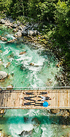 Aerial view of sporty family lying on wooden suspension bridge above a river.