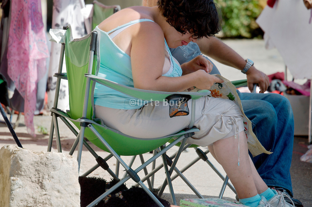 obese female person sitting and doing needlepoint