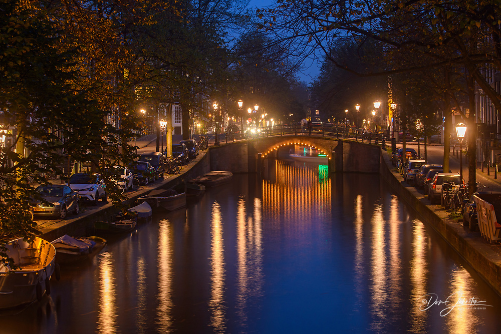Reflections of bridge lighting in canals at dusk, Amsterdam, North Holland, Netherlands