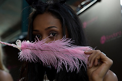© London News Pictures. 26/10/2013 . London, UK. A woman poses with a pink feather at the Erotica show at Tobacco Dock in East London on 25 October 2013. The three day event runs from 25 October until 27 October and features stalls selling sex toys and clothes and stage shows of exotic dancing. Photo credit : Vickie Flores/LNP