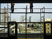 "23 AUGUST 2016 - NONTHABURI, NONTHABURI, THAILAND: Construction workers on scaffolding in the Tao Poon station of the ""Purple Line,"" the new Bangkok commuter rail line that runs from Bang Sue, in Bangkok, to Nonthaburi, a large Bangkok suburb. The Purple Line is run by the  Metropolitan Rapid Transit (MRT) which operates Bangkok's subway system. The Purple Line is the fifth light rail mass transit line in Bangkok and is 23 kilometers long. The Purple Line opened on August 6 and so far ridership is below expectations. Only about 20,000 people a day are using the line; officials had estimated as many 70,000 people per day would use the line. The Purple Line was supposed to connect to the MRT's Blue Line, which goes into central Bangkok, but the line was opened before the connection was completed so commuters have to take a shuttle bus or taxi to the Blue Line station. The Thai government has ordered transit officials to come up with plans to increase ridership. Officials are looking at lowering fares and / or improving the connections between the two light rail lines.     PHOTO BY JACK KURTZ"