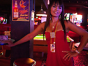 "12 JULY 2011 - BANGKOK, THAILAND:  A worker in the ""Corner Bar"" on Soi Cowboy in a ""red light"" district in Bangkok. Prostitution in Thailand is illegal, although in practice it is tolerated and partly regulated. Prostitution is practiced openly throughout the country. The number of prostitutes is difficult to determine, estimates vary widely. Since the Vietnam War, Thailand has gained international notoriety among travelers from many countries as a sex tourism destination. One estimate published in 2003 placed the trade at US$ 4.3 billion per year or about three percent of the Thai economy. It has been suggested that at least 10% of tourist dollars may be spent on the sex trade. According to a 2001 report by the World Health Organisation: ""There are between 150,000 and 200,000 sex workers (in Thailand).""  PHOTO BY JACK KURTZ"