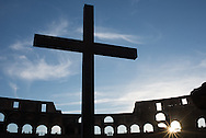 A cross stands erect as the sunsets over Rome from inside the Colosseum