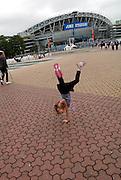 Child (6 years old) doing one-handed cartwheel outside Sydney Olympic Stadium. Sydney, Australia