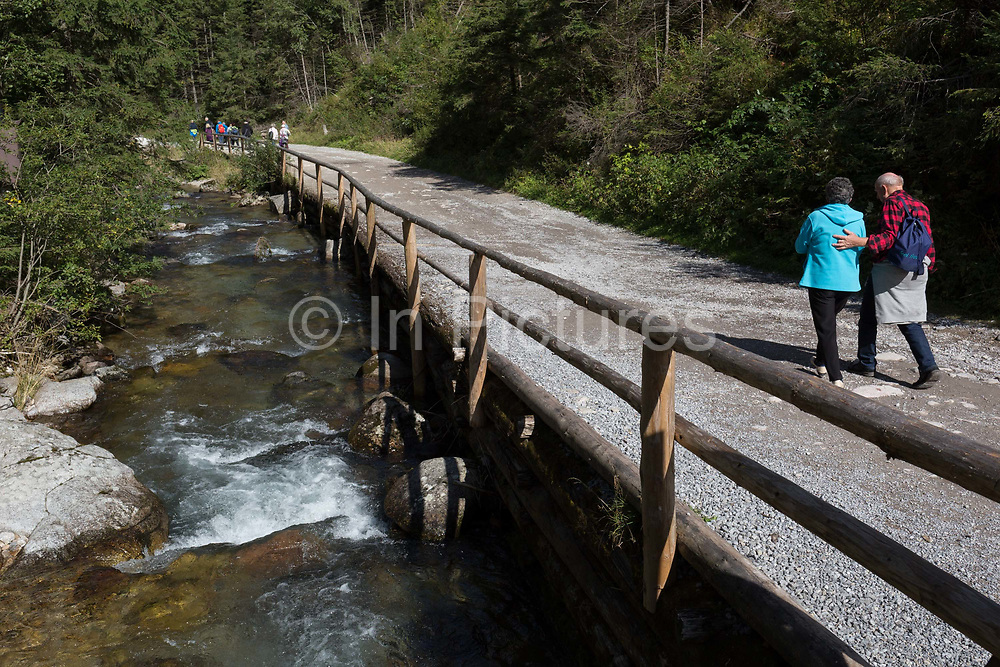 Two walkers make their way alongside the Siwa Woda river in Dolina Chocholowska, a hiking route in the Tatra National Park, on 17th September 2019, near Zakopane, Malopolska, Poland.