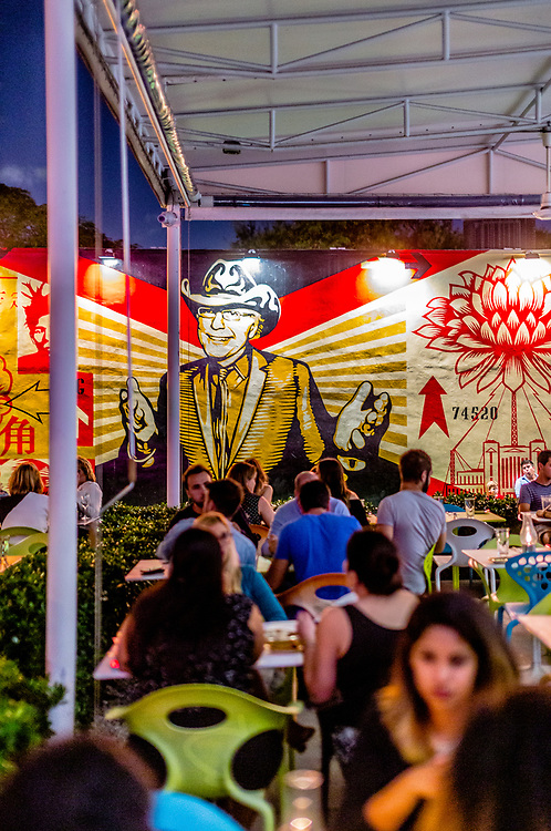 A Shepard Fairey mural of Miami real estate visionary Tony Goldman overlooks the bustling Wynwood Kitchen & Bar restaurant at The Wynwood Walls.
