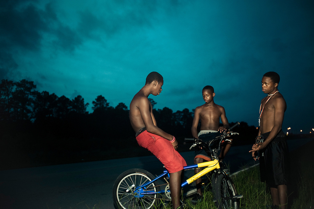 Copyright Joshua Cogan  Boys gather on a roadside to pass the time in Gulfport, MI.