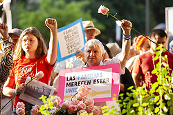 June 14, 2018 - Dallas, Texas, U.S. - Sylvia Collins,right, holds a  rose in front of Dallas City Hall in downtown Dallas as a protest against the policy of housing children separated from their parents at the border in tents by the Trump Administration. The protest was part of a national campaign, Families Belong Together, to condemn the treatment of immigrants and their children by ICE. (Credit Image: © Jaime R. Carrero via ZUMA Wire)