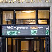 NLD/Amsterdam/20160121 - Winkels in het Amsterdamse straatbeeld, gebouw van Beursplein 5 Amsterdam met de koersen van AEX Experience en TNT Expressop de gevel