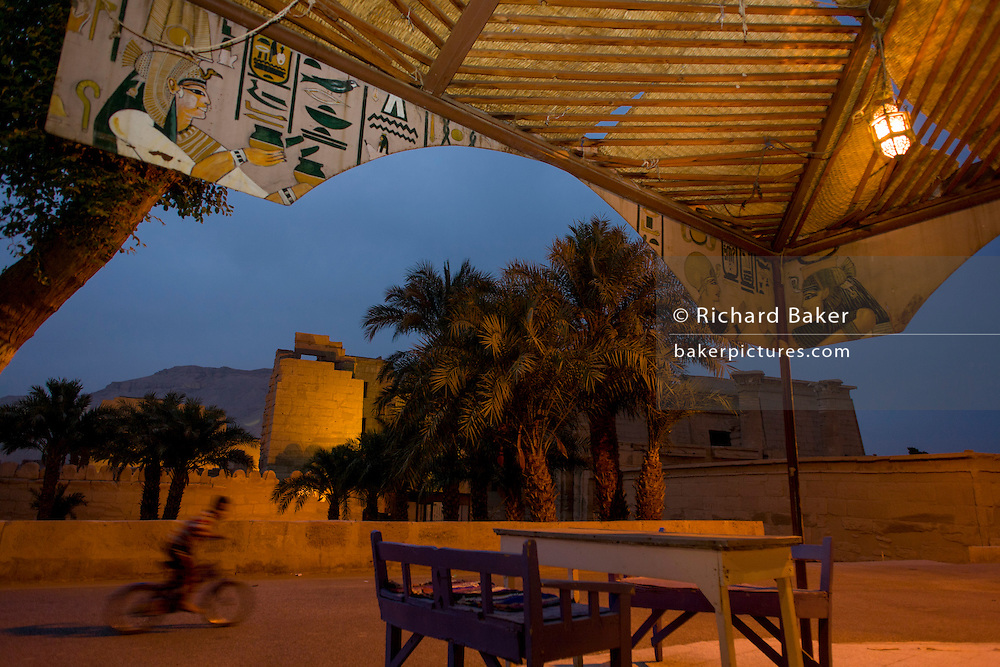 A quirky landscape of a modern-day street cafe's pharaonic illustrations and in the background, the ancient Egyptian site of Medinet Habu (1194-1163BC), the Mortuary Temple of Ramesses III in Luxor, Nile Valley, Egypt. Medinet Habu is an important New Kingdom period structure in the West Bank of Luxor in Egypt. Aside from its size and architectural and artistic importance, the temple is probably best known as the source of inscribed reliefs depicting the advent and defeat of the Sea Peoples during the reign of Ramesses III.