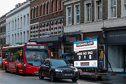 © Licensed to London News Pictures. 23/12/2020. London, UK. A huge coronavirus alert sign warning members of the public to be vigilant appears in Putney, South West London as Health Secretary Matt Hancock announced in a televised address to the Nation that yet another new Covid-19 mutation has been discovered in South Africa and is already in the UK as Downing Street orders many more areas of England to go into Tier 4. Tougher Covid-19 restrictions have already been implemented in London after the UK mutated strain continues to spread throughout  the South East . Photo credit: Alex Lentati/LNP
