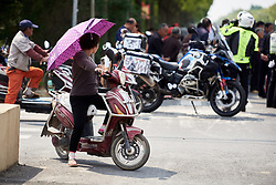 Local waits on her own wheels for the race to arrive at Tour of Chongming Island 2019 - Stage 1, a 102.7 km road race on Chongming Island, China on May 9, 2019. Photo by Sean Robinson/velofocus.com