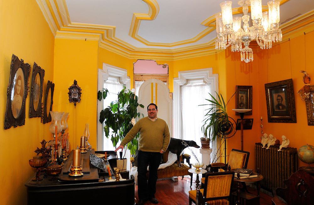 Matt Dixon | The Flint Journal..Michael Freeman, owner of the historic Mason House poses for a portrait in the parlor, which was once a studio apartment when the building was rented as five units. Freeman has been restoring the house with the help of his family since he purchased it in 1994.