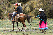 Woman pulls tail of horse ridden by two children in Yanajanca Valley. Day 5 of 10 days trekking around Alpamayo, in Huascaran National Park, Cordillera Blanca, Andes Mountains, Peru, South America.