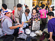 """09 JUNE 2013 - BANGKOK, THAILAND:  White Mask protesters buy Guy Fawkes masks in front of Central World Mall before an anti-government protest. The White Mask protesters wear the Guy Fawkes mask popularized by the movie """"V for Vendetta"""" and the protest groups Anonymous and Occupy. Several hundred members of the White Mask movement gathered on the plaza in front of Central World, a large shopping complex at the Ratchaprasong Intersection in Bangkok, to protest against the government of Thai Prime Minister Yingluck Shinawatra. They say that her government is corrupt and is a """"puppet"""" of ousted (and exiled) former PM Thaksin Shinawatra. Thaksin is Yingluck's brother. She was elected in 2011 when her brother endorsed her.   PHOTO BY JACK KURTZ"""