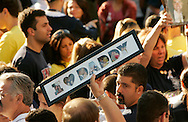 A family member of a victim of the World Trade Center attack holds a commemorative set of pictures at the site of the disaster on the fourth anniversary of the attack in New York September 11, 2005.