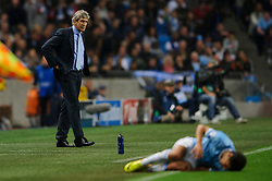 Man City Manager Manuel Pellegrini (CHI) looks on as Midfielder Jesus Navas (ESP) goes down during the first half of the match - Photo mandatory by-line: Rogan Thomson/JMP - Tel: Mobile: 07966 386802 - 02/10/2013 - SPORT - FOOTBALL - Etihad Stadium, Manchester - Manchester City v Bayern Munich - UEFA Champions League Group D.