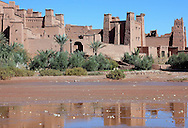UNESCO World heritage site Kasbah Ait Ben Haddou with water reflections and blue sky.