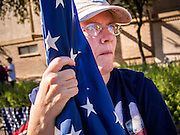 "11 NOVEMBER 2013 - PHOENIX, AZ:  A woman holds an American flag while she watches the Phoenix Veterans Day Parade. The Phoenix Veterans Day Parade is one of the largest in the United States. Thousands of people line the 3.5 mile parade route and more than 85 units participate in the parade. The theme of this year's parade is ""saluting America's veterans.""    PHOTO BY JACK KURTZ"