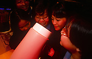 Young women students enjoy interacting with the latest 1990s technology ideas at a Cable & Wireless exhibition, on 29th March 1996, in Hong Kong, China.