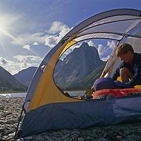 Glacier Lake, Logan Mountains, Northwest Territories, Canada.A camper unpacks in his tent under Mount Harrison Smith.