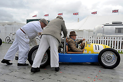 © Licensed to London News Pictures. 17/09/2011. GOODWOOD, UK. Drivers and mechanics prepare their cars before racing. The Goodwood Revival at Goodwood in West Sussex today (17 September 2011). The revival is the world's largest historic motor race meeting, which relieves the 'glorious' days of the race circuit. Competitors and enthusiasts all dress in period fashion to enhance the experience. Photo credit : Stephen Simpson/LNP