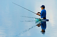 KEVIN BARTRAM/The Daily News<br /> A fisherman tries his luck in the lagoon near Boddecker Drive on the east end of Galveston early Wednesday morning, August 24, 2005.