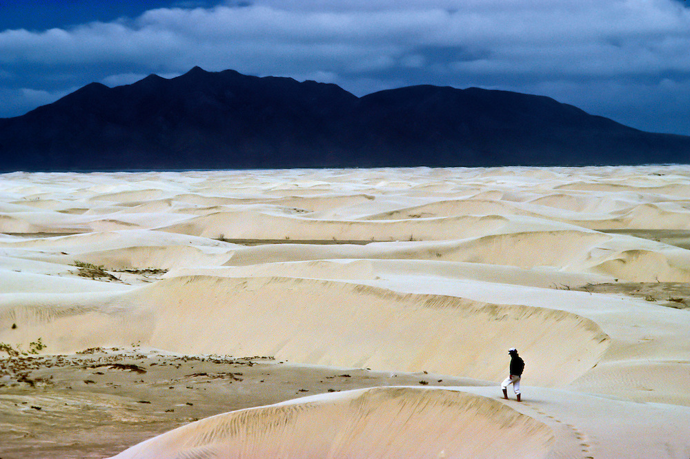 A man explores the dunes against the water in Baja California.