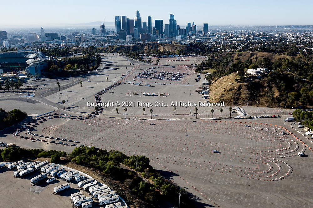 Motorists wait in lines to get the coronavirus (COVID-19) vaccine in a parking lot at Dodger Stadium, Friday, Jan. 15, 2021, in Los Angeles. Dodger Stadium reopened Friday as a mass COVID-19 vaccination site, which Mayor Eric Garcetti says will have the capacity to vaccinate 12,000 people a day once it is fully operational.