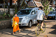 11 MARCH 2013 - LUANG PRABANG, LAOS:  A Buddhist novice going to Wat Xieng Thong, the most historic Buddhist temple in Luang Prabang, talks to a bicyclist pedaling past the temple.   PHOTO BY JACK KURTZ