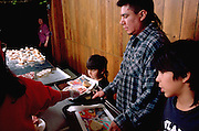 Family served Christmas dinner by volunteers church soup kitchen.  Minneapolis Minnesota USA