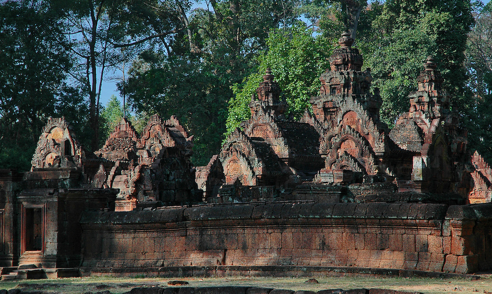 This image of Banteay Srei, a richly decorated, late 10th century Hindu temple dedicated to Shiva is located in the Angkor Wat temple complex in Siem Reap, Cambodia.<br /> <br /> The temple is built in red sandstone and has beautiful bas-reliefs and decorations. It is surrounded by three enclosures with the central structure being surrounded by a moat. <br /> <br /> Built at a time when the Khmer Empire was gaining significant power and territory, the temple was constructed by a Brahmin counselor under a powerful king, Rajendravarman and later under Jayavarman V. Banteay Srey displays some of the finest examples of classical Khmer art. The walls are densely covered with some of the most beautiful, deep and intricate carvings of any Angkorian temple. The temple's relatively small size, pink sandstone construction and ornate design give it a fairyland ambiance.<br /> <br /> This temple was discovered by French archaeologists relatively late, in 1914.