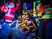 """23 DECEMBER 2018 - CHANTABURI, THAILAND: Siblings play cotton balls the represent snow in the """"North Pole"""" at the Cathedral of the Immaculate Conception's Christmas Fair in Chantaburi. Cathedral of the Immaculate Conception is holding its annual Christmas festival, this year called """"Sweet Christmas @ Chantaburi 2018"""". The Cathedral is the largest Catholic church in Thailand and was founded more than 300 years ago by Vietnamese Catholics who settled in Thailand, then Siam.   PHOTO BY JACK KURTZ"""