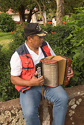 Chile, Easter Island: Man playing accordion..Photo #: ch342-33081..Photo copyright Lee Foster www.fostertravel.com lee@fostertravel.com 510-549-2202