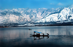 """Kashmiris take a Sunday afternoon """"shikari""""  or gondola on Dal Lake with the Himalayas as a backdrop in Srinigar, February 10, 2002 in the Indian held state of Kashmir. India and Pakistan have already fought three wars over Kashmir and are the brink again as they amass their troops along the Line of Control. (Ami Vitale/Getty Images)"""
