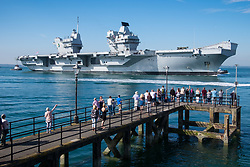 © Licensed to London News Pictures. 23/06/2018. Portsmouth, UK.  People watching and waving as the Royal Navy's flagship, HMS Queen Elizabeth, sails into Her Majesty's Naval Base (HMNB) Portsmouth this morning, 23rd June 2018.  The aircraft carrier has been performing trials in the Northern Atlantic, including her first replenishment at sea. She is expected to remain in Portsmouth ahead of aircraft trials off the coast of the United States later this summer.Photo credit: Rob Arnold/LNP