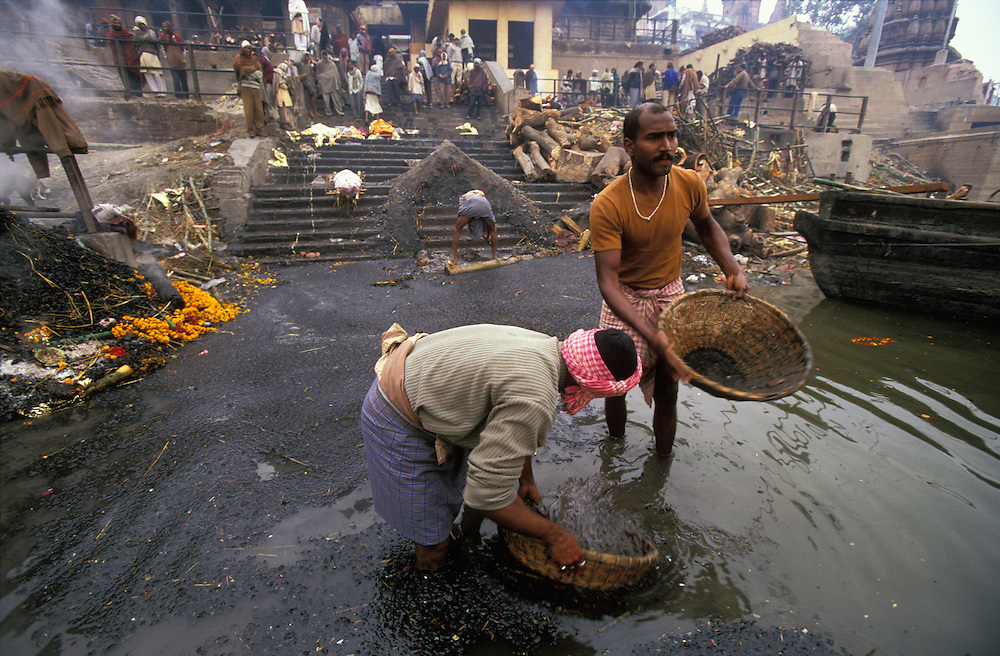 Cremation workers called Dom, and classed as untouchables, clear the river Ganges from charcoal and other debris, while also looking for valuables at Manikarnika Ghat, the main cremation site of Varanasi, India. On the steps lie biers with dead bodies waiting to be cremated. To be cremated in the sacred city of Varanasi means a straight passage to heaven, many Hindus believe.