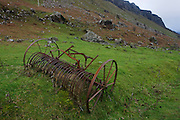 Old horse-drawn reaper lying in field at Gribun, Isle of Mull, Scotland.