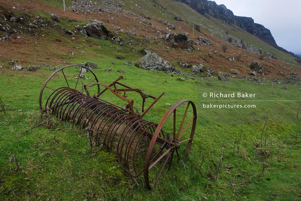 Old horse-drawn reaper lying in field at Gribun, Isle of Mull, Scotland.