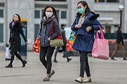 March 14, 2020, London, England, United Kingdom: People wearing face masks walk along a main shopping area at Canary Wharf in London, Saturday, March 14, 2020. For most people, the new COVID-19 coronavirus causes only mild or moderate symptoms, such as fever and cough. For some, especially older adults and people with existing health problems, it can cause more severe illness, including pneumonia. (Credit Image: © Vedat Xhymshiti/ZUMA Wire)