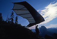 A hang glider pilot get his kite in the exact position for a successful launch off Glacier Point.  The sport in the park is allowed and is regulated and monitored by rangers.  July 1989.