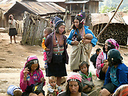 A group of Akha Cherpia women and their children wearing a mixture of traditional and modern clothing in Ban Nam Hin village, Phongsaly Province, Lao PDR.  One of the most ethnically diverse countries in Southeast Asia, Laos has 49 officially recognised ethnic groups although there are many more self-identified and sub groups. These groups are distinguished by their own customs, beliefs and rituals. Details down to the embroidery on a shirt, the colour of the trim and the type of skirt all help signify the wearer's ethnic and clan affiliations.