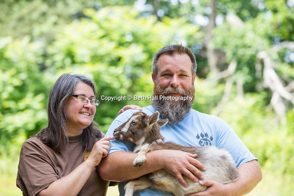 Tessa McCormick stands next to Scott McCormick as he holds a baby goat at White River Creamery on Friday, June 20, 2014 in Elkins, Ark.<br /> <br /> Photo by Beth Hall