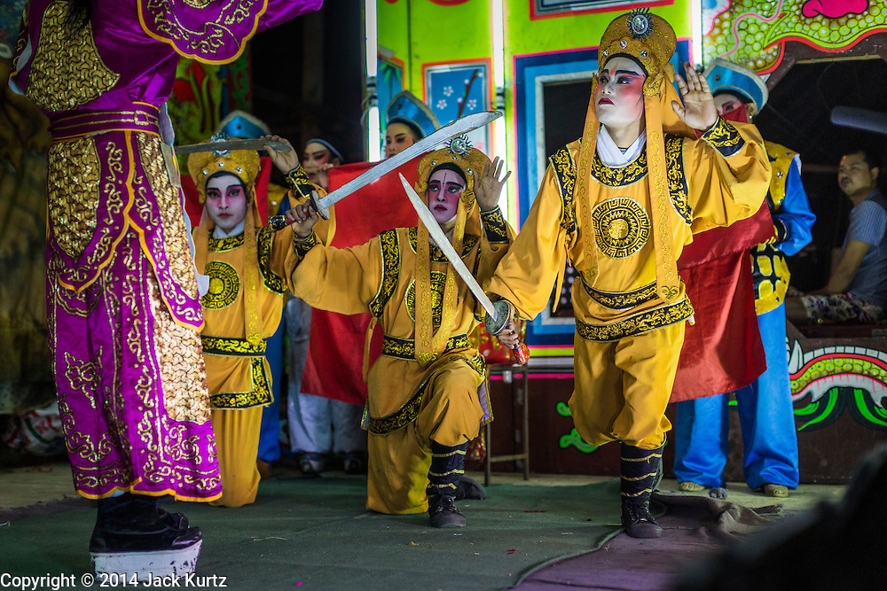 "25 JANUARY 2014 - BANG LUANG, NAKHON PATHOM, THAILAND: The Sing Tong Teochew opera troupe performs in a Chinese shrine in the village of Bang Luang, Nakhon Pathom, Thailand. The Sing Tong Teochew opera troupe has been together for 60 years and travels through central Thailand and Bangkok performing for mostly ethnic Chinese audiences.  Chinese opera was once very popular in Thailand, where it is called ""Ngiew."" It is usually performed in the Teochew language. Millions of Chinese emigrated to Thailand (then Siam) in the 18th and 19th centuries and brought their cultural practices with them. Recently the popularity of ngiew has faded as people turn to performances of opera on DVD or movies. There are still as many 30 Chinese opera troupes left in Bangkok and its environs. They are especially busy during Chinese New Year when travel from Chinese temple to Chinese temple performing on stages they put up in streets near the temple, sometimes sleeping on hammocks they sling under their stage.     PHOTO BY JACK KURTZ"