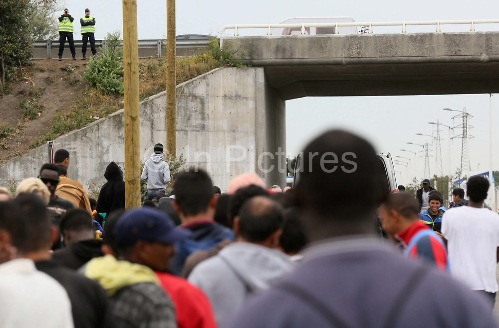 Police observe migrants in 'the Jungle' migrant camp in Calais, France, August 10, 2015. The Calais jungle is the nickname given to a series of camps in the vicinity of Calais, France, where migrants live while they attempt to enter the United Kingdom illegally by stowing away on lorries, ferries, cars, or trains travelling through the Port of Calais or the Eurotunnel Calais Terminal. The migrants are a mix of refugees, asylum seekers and economic migrants from Darfur, Afghanistan, Syria, Iraq, Eritrea and other troubled areas of the world.