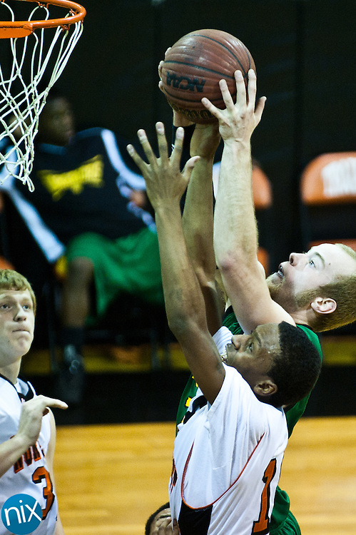 Northwest Cabarrus's Ameer Jackson and West Iredell's Matt Harris fight for a rebound Monday night at Northwest Cabarrus in the first round of NCHSAA 3-A Playoffs. Northwest Cabarrus won 67-61 to advance. (Photo by James Nix)