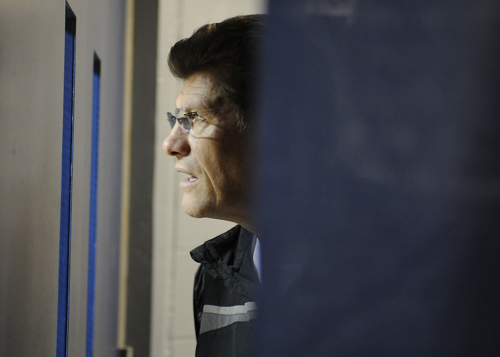 Connecticut head coach Geno Auriemma watches the looks out a window to watch the men's basketball team practice at the University of Connecticut in Storrs, Conn., Thursday, March 3, 2011  (AP Photo/Jessica Hill)